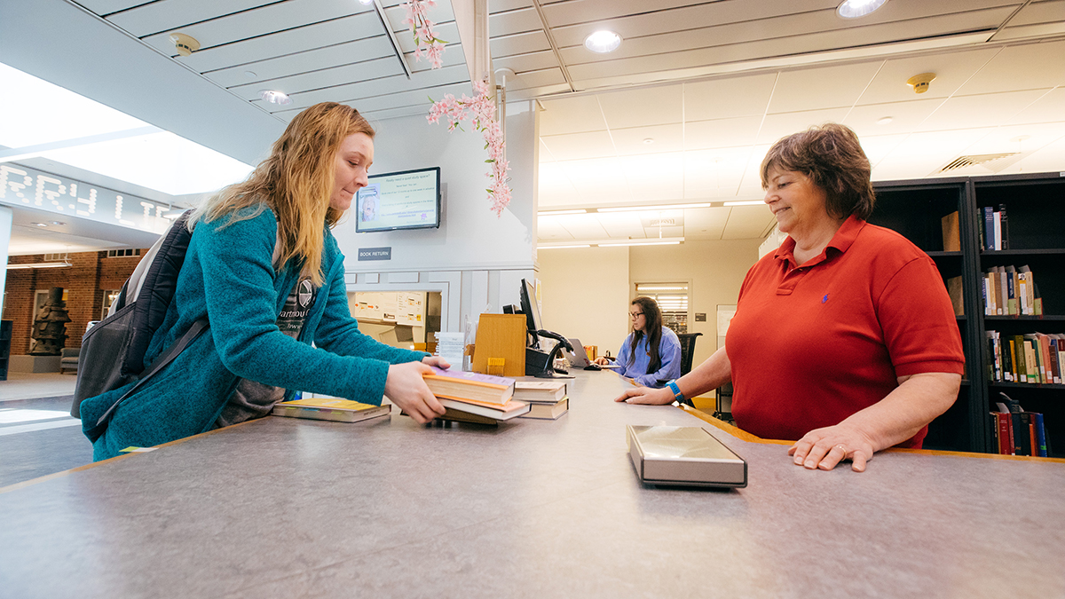 Student returns books to the Baker-Berry Circulation Desk