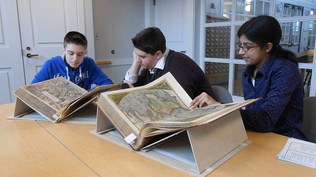 Students look at a large book in Rauner
