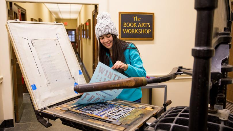 Woman prints a winter carnival poster at Dartmouth Library