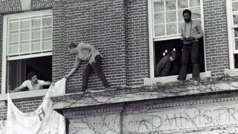 Students climb through windows and hang sign outside Parkhurst Hall