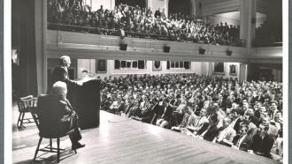 Professor addresses students in large hall