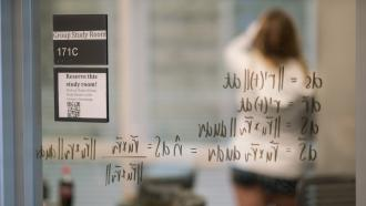 A student writes on the glass walls of a study room in Baker-Berry Library at Dartmouth College