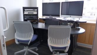 A room with a desk, chairs and computers