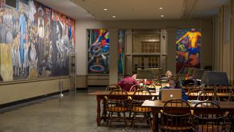 Murals on the walls and students sitting tables