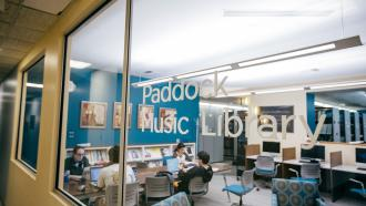 Writing on window says Paddock Library and students studying